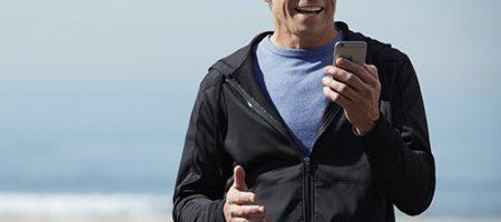 Homme utilisant des aides auditives connectées à son smartphone
